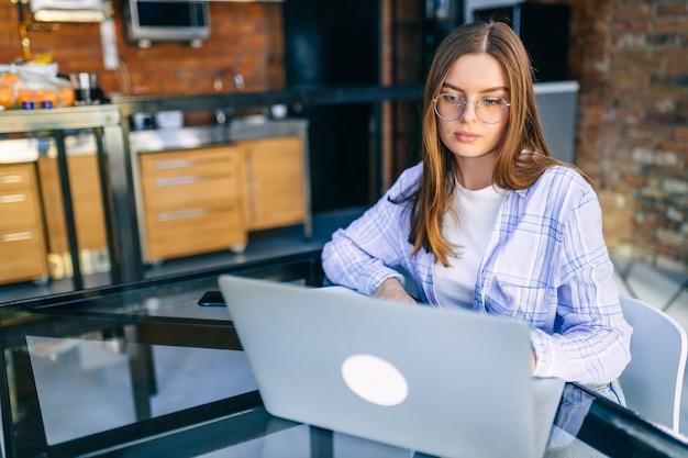 Молодой концентрированный бизнесвумен в очках и рубашке, работающий с ноутбуком дома