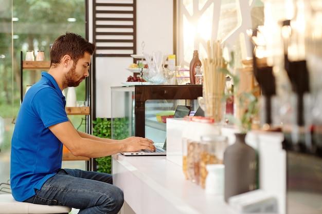 Молодой сосредоточенный владелец кофейни работает за ноутбуком, сидя за стойкой и ожидая клиентов