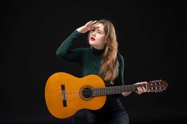 Young concentrated female guitarist holding her favorite musical instrument on dark