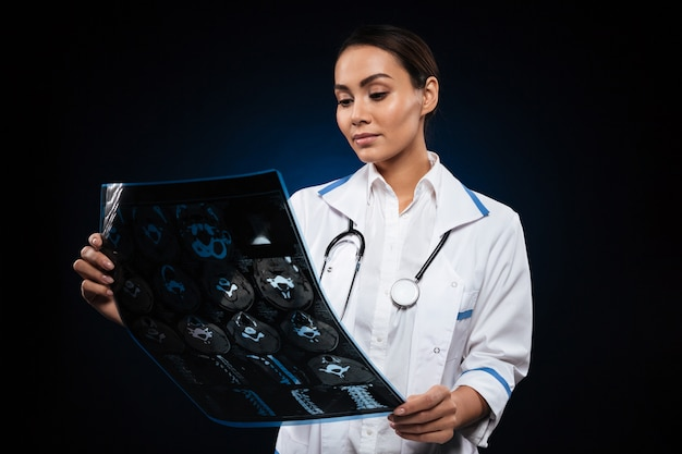 Young concentrated lady looking at x-ray image isolated