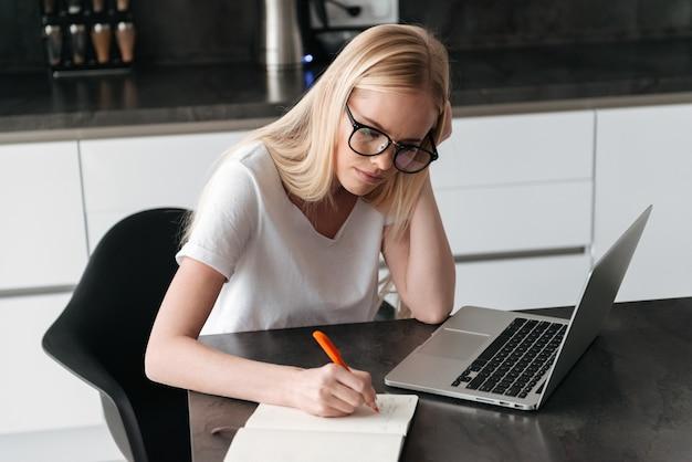 Молодая сосредоточенная дама работая дома с компьтер-книжкой и тетрадью