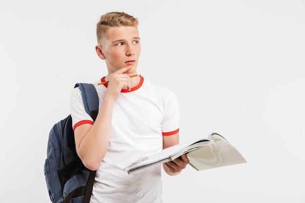 Молодой сконцентрированный ученик в рюкзаке думает и смотрит в сторону, изучая учебники и ручку в руках, изолированных на белом