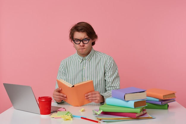 Giovane uomo concentrato in bicchieri indossa una camicia, si siede al tavolo e lavora con il taccuino, preparato per l'esame, legge il libro, sembra serio, isolato su sfondo rosa.