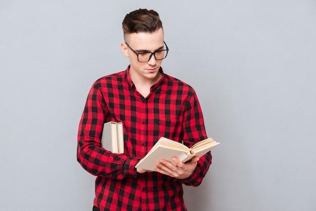 Молодой концентрированный человек в очках, читая книгу в студии. изолированный серый фон