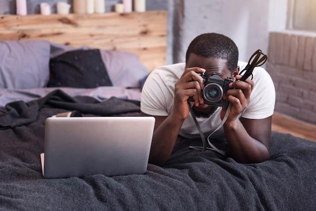 寝室に横たわっている間写真を作り、写真カメラを保持している若い集中男