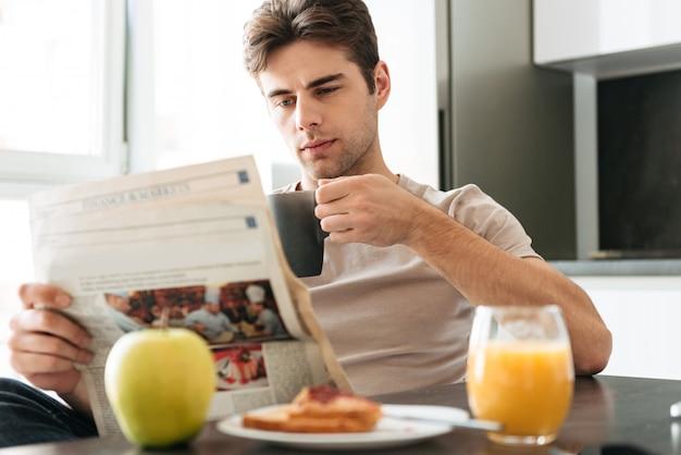 Молодой концентрированный человек читает газету, сидя на кухне