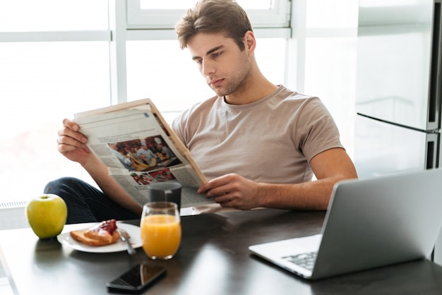 Young concentrated man reading newspaper while sitting in kitchen