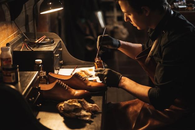 若い集中男靴屋で靴屋。