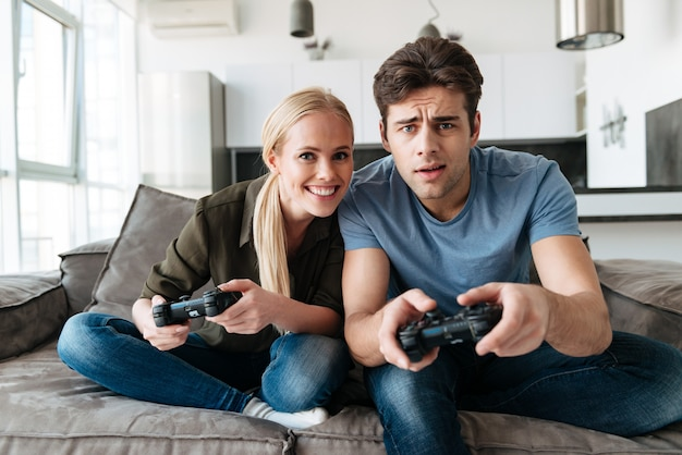 Young concentrated man and woman playing video games in living room