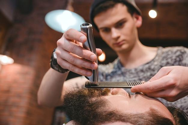 Молодой сосредоточенный опытный парикмахер делает идеальную бороду красивому бородатому мужчине с помощью триммера и расчески в парикмахерской