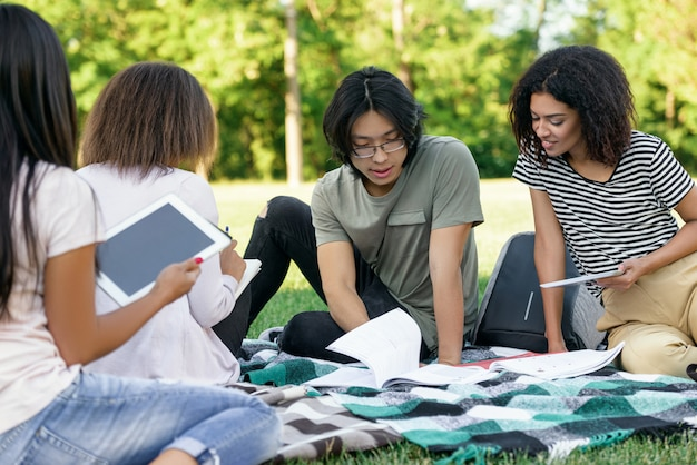 Молодые сосредоточены студенты, обучающиеся на открытом воздухе.