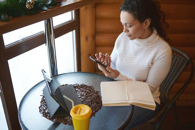 Молодая концентрированная женщина проверяет свой мобильный телефон, сидя у окна в деревянном кафе
