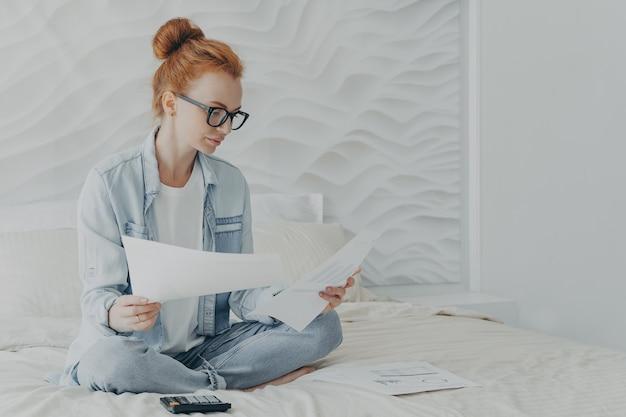 Молодая сосредоточенная женщина-домохозяйка в очках управляет семейным бюджетом, сидя на кровати дома