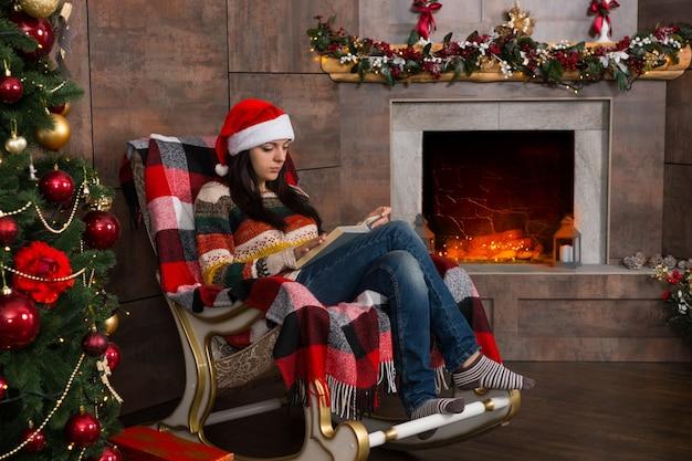 装飾された暖炉のあるリビングルームのクリスマスツリーの近くのロッキングチェアに座って面白いクリスマスの帽子を読んで若い集中女性