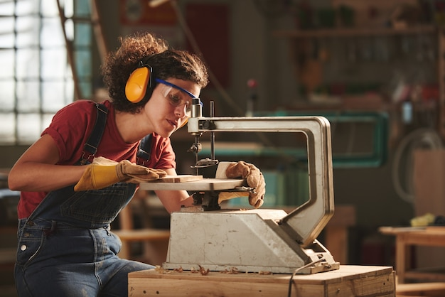 Young concentrated woman in protective eyewear and earmuffs making holes in wooden plank with drill press