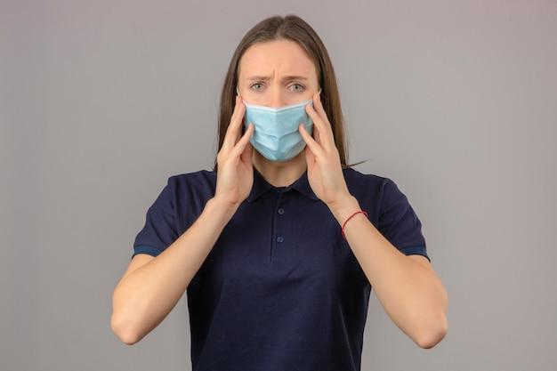 Молодая обеспокоенная и взволнованная женщина, одетая в синюю футболку в защитной медицинской маске, смотрит на камеру с поднятыми руками, касаясь ее маски на светло-сером фоне изолированные