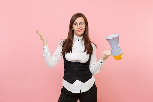 Young concerned business woman in black suit and glasses holding megaphone and spreading hands isolated on pink background. lady boss. achievement career wealth concept. copy space for advertisement.