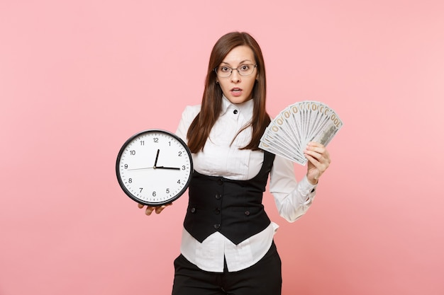 Young concerned business woman in glasses holding bundle lots of dollars, cash money and alarm clock isolated on pink background. lady boss. achievement career wealth. copy space for advertisement.