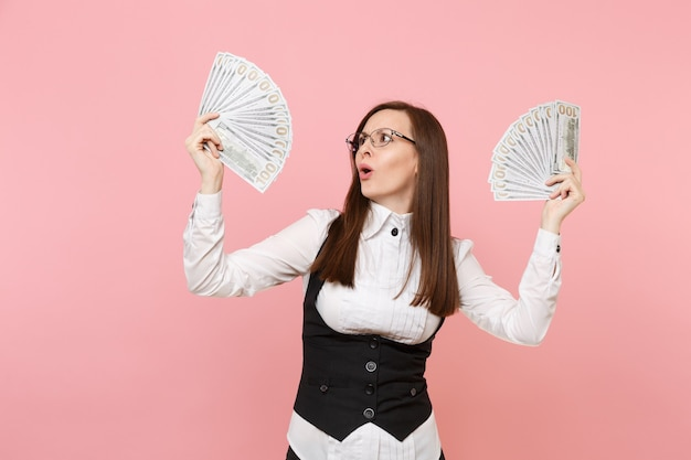 Young concerned business woman in glasses holding bundle lots of dollars, cash money spreading hands isolated on pink background. lady boss. achievement career wealth. copy space for advertisement.