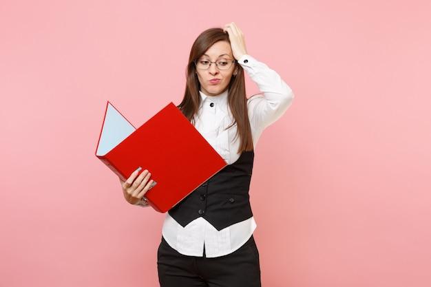 서류 문서용 빨간색 폴더를 들고 분홍색 배경에 격리된 머리에 집착하는 안경을 쓴 젊은 걱정스러운 비즈니스 여성. 여사장님. 성취 경력 부입니다. 광고 공간을 복사합니다.
