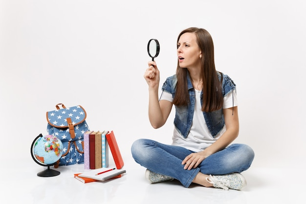 Young concerned casual woman student holding looking on magnifying glass sitting near globe, backpack, school books isolated