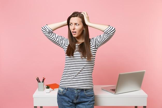 パステルピンクの背景で隔離のラップトップと白い机の近くに立って頭の仕事にしがみついているカジュアルな服を着た若い心配の女の子。業績ビジネスキャリアコンセプト。広告用のスペースをコピーします。