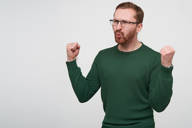 Giovani interessati a pelo corto maschio bruna con la barba che alza i pugni e le sopracciglia accigliate mentre guarda da parte, vestito con un maglione verde mentre posa