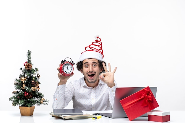 Young concerned surprised business person with santa claus hat and holding clock and showing three in the office on white background