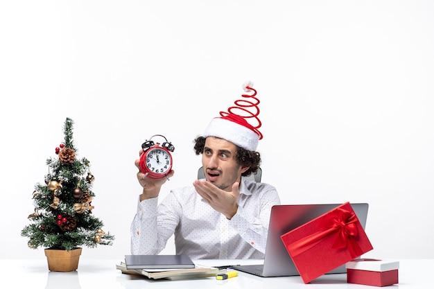 Giovane uomo d'affari sorpreso interessato con cappello di babbo natale e holding e guardando l'orologio in ufficio su sfondo bianco