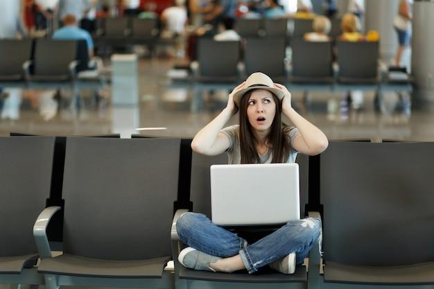 Giovane turista viaggiatrice preoccupata con laptop seduto con le gambe incrociate aggrappate alla testa mentre aspetta nella hall dell'aeroporto