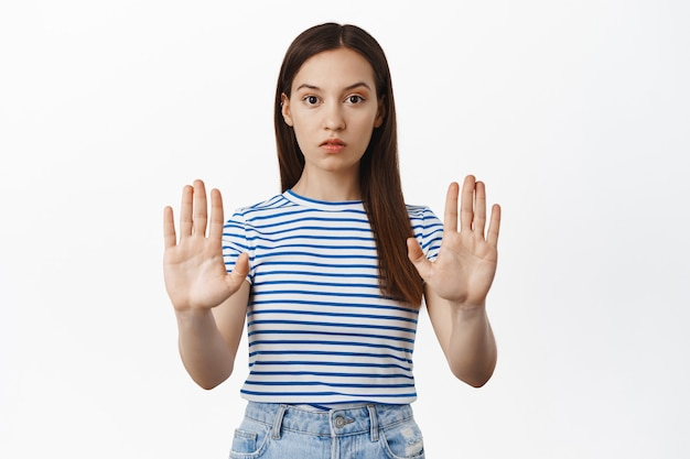 Young concerned woman extend hands, stretch out palms in taboo, no block gesture, refuse smth, disapprove and prohibit action, standing against white wall
