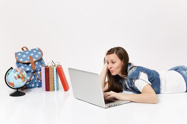 Giovane studentessa preoccupata in abiti di jeans che lavora su un computer portatile sdraiato vicino a globo, zaino, libri scolastici