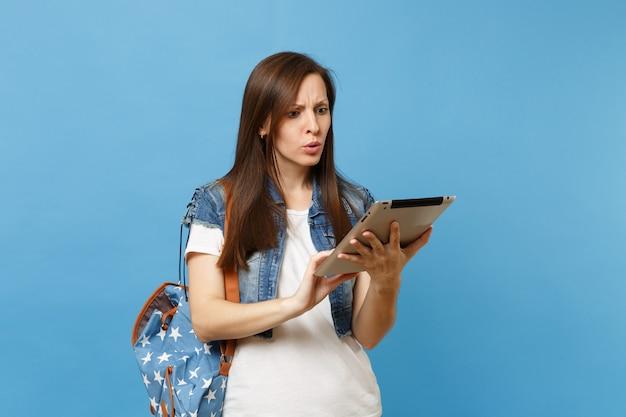 티셔츠를 입은 젊은 여성 학생, 배낭을 든 데님 옷, 파란색 배경에 격리된 태블릿 pc 컴퓨터 작업을 사용합니다. 대학에서 교육입니다. 광고 공간을 복사합니다.