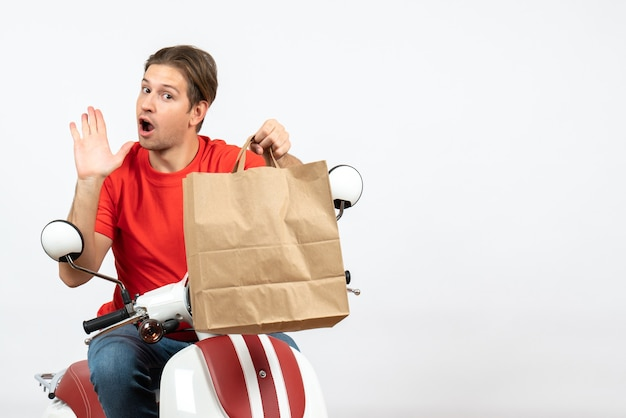Young concerning courier guy in red uniform sitting on scooter holding paper bag on white wall