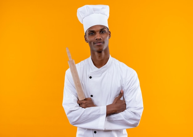 Young confident afro-american cook in chef uniform crosses arms and holds rolling pin isolated on orange background with copy space