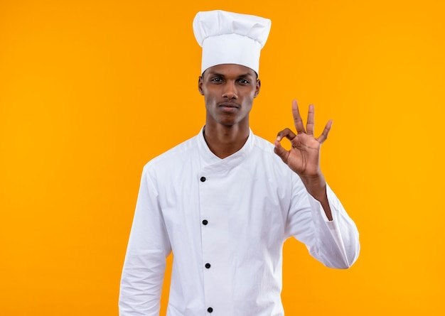 Young confident afro-american cook in chef uniform gestures ok isolated on orange background with copy space