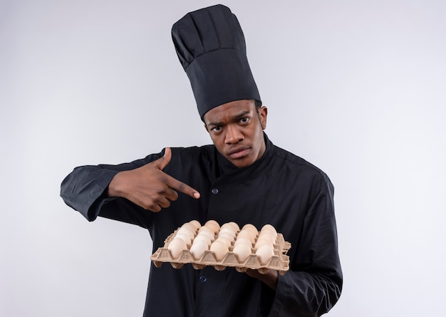 Young confident afro-american cook in chef uniform holds batch of eggs and points with finger isolated on white background with copy space
