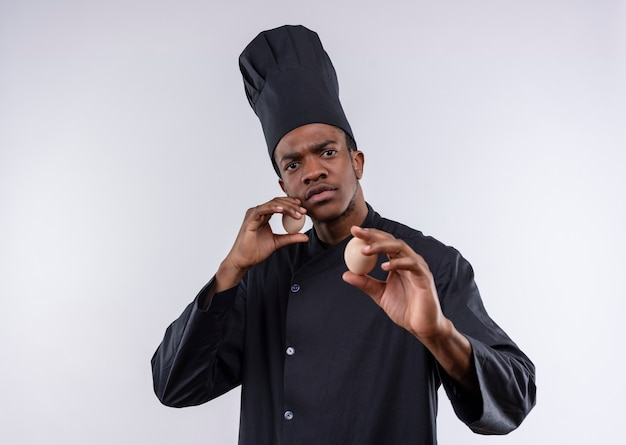 Young confident afro-american cook in chef uniform holds eggs and pretends to defend isolated on white background with copy space