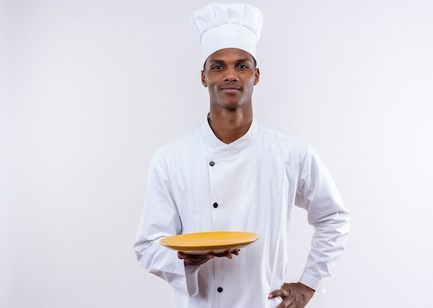Young confident afro-american cook in chef uniform holds empty plate and puts hand on waist on isolated white background with copy space