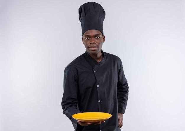 Il giovane cuoco afroamericano sicuro in uniforme del cuoco unico tiene il piatto vuoto e mette la mano sulla vita su bianco con lo spazio della copia