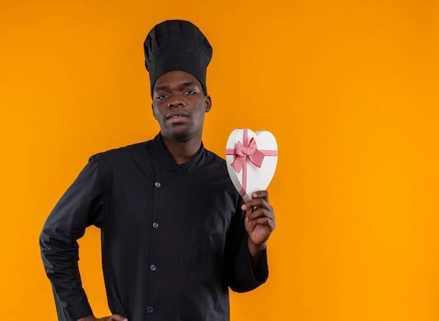 Il giovane cuoco afroamericano fiducioso in uniforme da chef tiene la scatola a forma di cuore e guarda la telecamera sull'arancio con lo spazio della copia