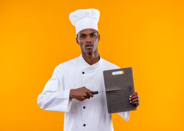 Il giovane cuoco afroamericano fiducioso in uniforme da chef tiene lo scrittorio della cucina e il coltello isolato su priorità bassa arancione con lo spazio della copia