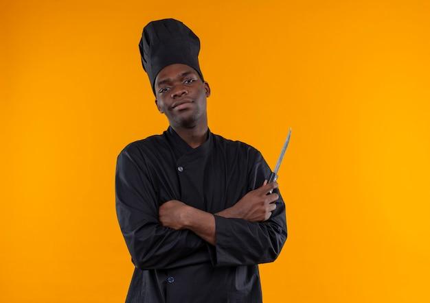 Il giovane cuoco afroamericano fiducioso in uniforme da chef tiene il coltello con le braccia incrociate isolato su priorità bassa arancione con lo spazio della copia