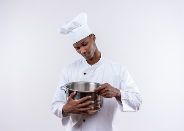 Young confident afro-american cook in chef uniform holds and looks at saucepan on isolated white background with copy space