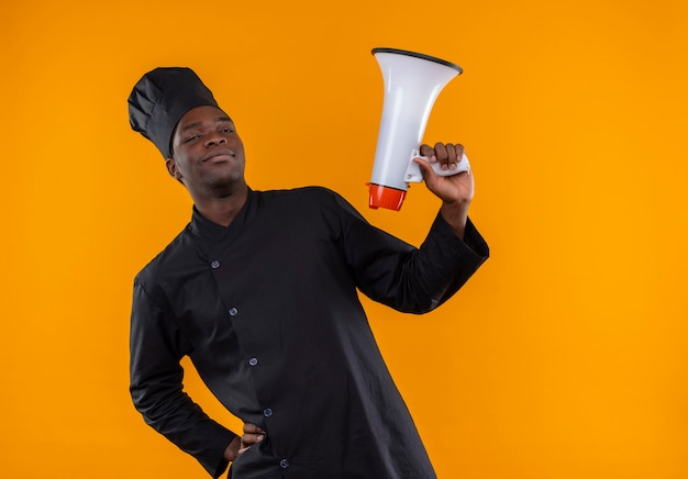 Young confident afro-american cook in chef uniform holds loud speaker on orange  with copy space