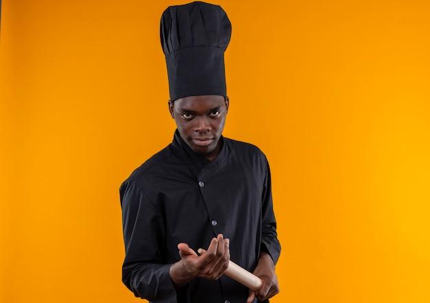 Il giovane cuoco afroamericano fiducioso in uniforme dello chef tiene il mattarello sull'arancia con lo spazio della copia