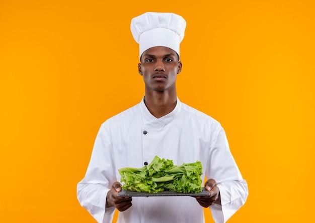 Il giovane cuoco afroamericano fiducioso in uniforme del cuoco unico tiene l'insalata sullo scrittorio della cucina con entrambe le mani isolate su fondo arancio con lo spazio della copia