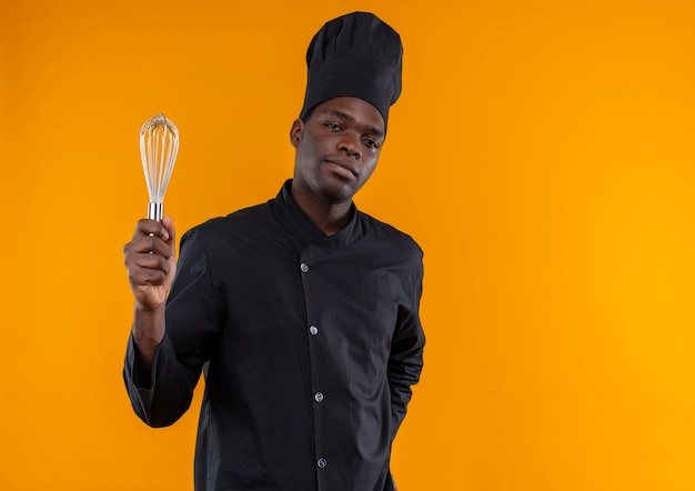 Giovane fiducioso afro-americano cuoco in uniforme da chef detiene la frusta guardando la telecamera isolata su sfondo arancione con copia spazio