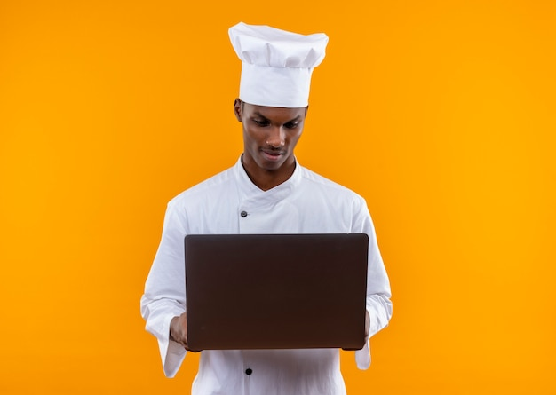 Young confident afro-american cook in chef uniform looks at laptop isolated on orange background with copy space