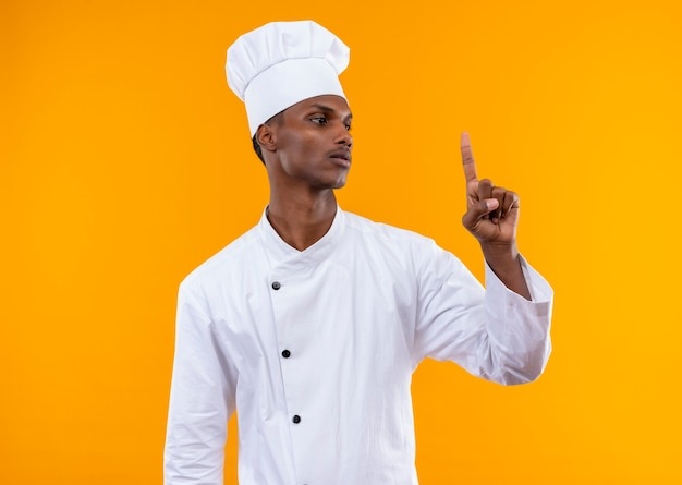 Young confident afro-american cook in chef uniform points up and looks at finger isolated on orange background with copy space
